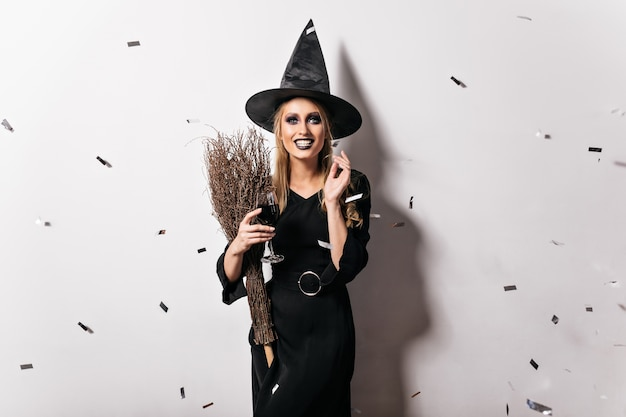 Marzycielska zła wiedźma pije wino. ekstatyczna młoda kobieta o blond włosach uśmiecha się na imprezie z okazji halloween.