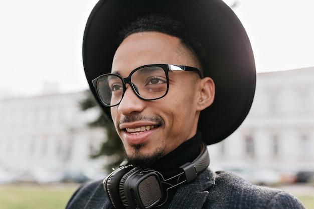 Marzycielski afrykański mężczyzna z dużymi brązowymi oczami odwracającymi wzrok. zewnątrz zdjęcie przystojny mężczyzna czarny model pozowanie