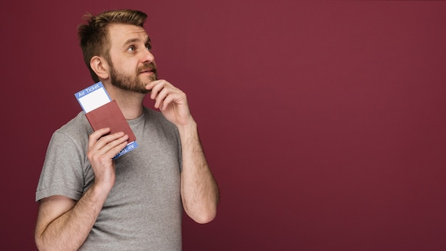 Marzycielski brodaty mężczyzna w koszulce trzymający bilety lotnicze i paszport na rubinowym tle