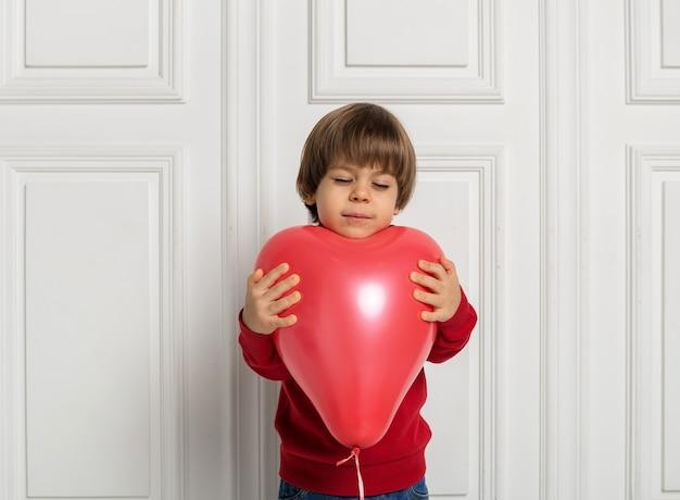 Marzycielski chłopiec trzymając serce czerwony balon na białym tle