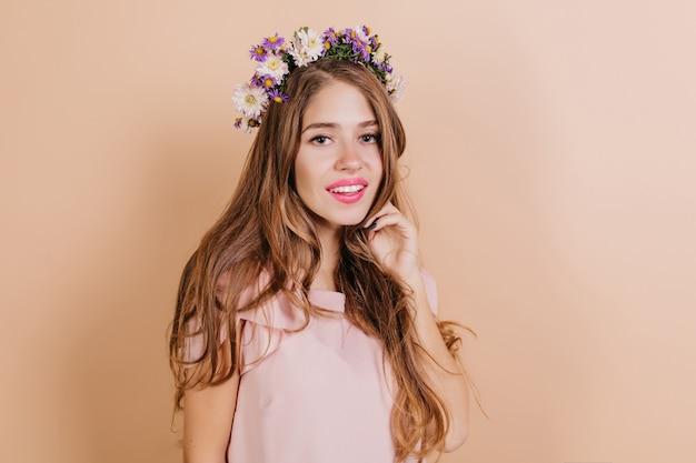 Marzycielski długowłosy brunetka kobieta z fioletowymi kwiatami we włosach uśmiecha się do kamery
