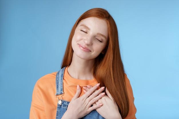 Marzycielski dotyk romantyczna ruda dziewczyna zamknij oczy przywołując wzruszający romans dotyk serca dłonie przyciśnięta klatka piersiowa uśmiechnięty czule czuć miłość troska współczucie wyrazić uczucia niebieskie tło