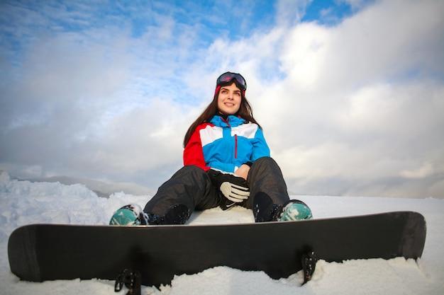 Marzycielski kobiety snowboarder siedzi na górze góry na niebieskim niebie