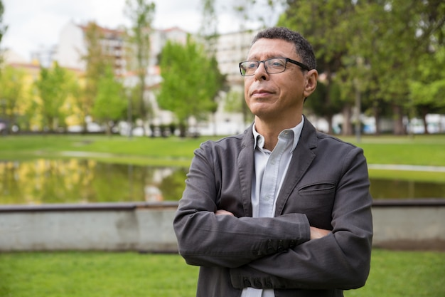 Marzycielski mężczyzna w średnim wieku stojący w parku miejskim