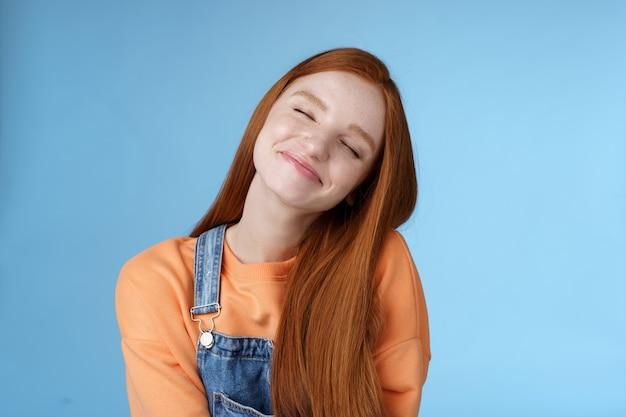 Marzycielski miły głupi rudowłosy uśmiechnięta szczęśliwa dziewczyna proste długie rude włosy marzenia wyobraź sobie romantyczny moment zamknij oczy uśmiechnięty zachwycony przechylana głowa wygląd radosny stojący niebieskie tło