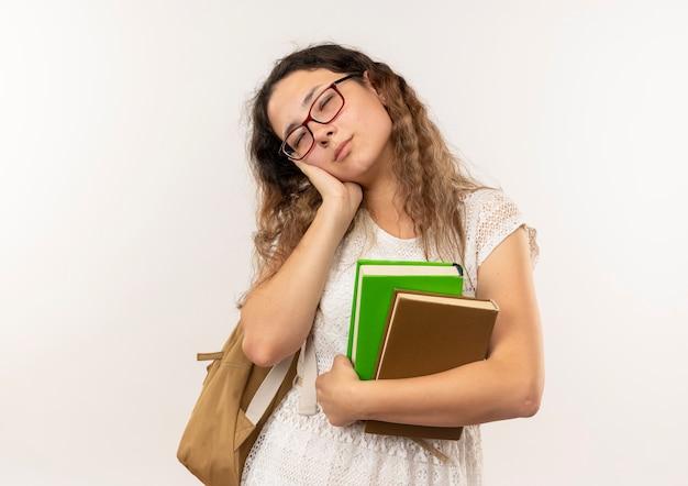 Marzycielski młoda ładna uczennica w okularach iz powrotem trzymając książki robi gest snu na białym tle na biały z miejsca na kopię