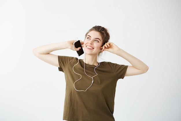 Marzycielski młoda piękna kobieta uśmiechnięta słuchanie muzyki w słuchawkach