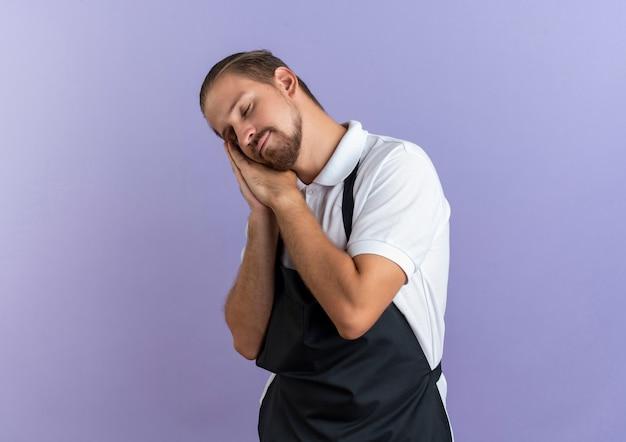 Marzycielski młody przystojny fryzjer w mundurze robi gest snu z zamkniętymi oczami na fioletowym tle z miejsca na kopię