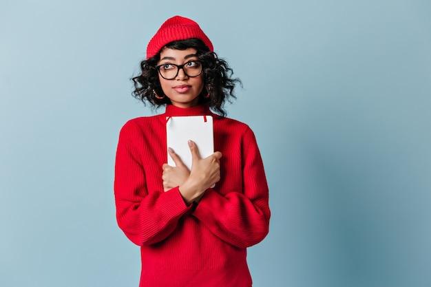 Marzycielski młody uczeń trzyma notatnik
