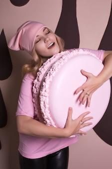 Marzycielski model blondynka w różowej koszulce i czapce bawi się z dużym ciastem makaronikiem. koncepcja wakacji