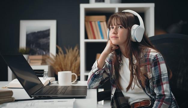Marzycielski nastolatek siedzi przed laptopem, opierając brodę na pięści, patrząc na bok, ucząc się w domu