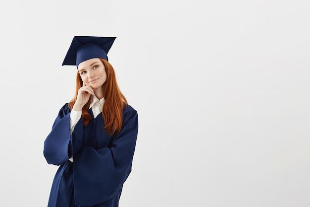Marzycielski piękna kobieta myśli absolwent marzy na białej powierzchni