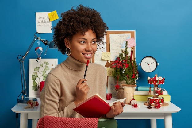 Marzycielski pozytywny student studiuje daleko podczas kwarantanny, siedzi blisko miejsca pracy, robi notatki w dzienniku, planuje przygotowania do egzaminu, tworzy nowy wiersz, pisze tekst, stara się zorganizować czas wolny