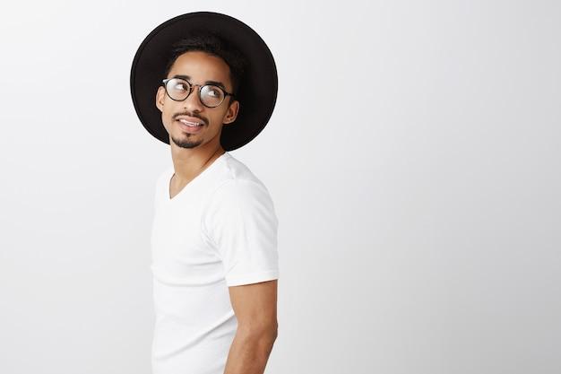 Marzycielski przystojny afroamerykanin w stylowym stroju odwraca się, patrząc w prawo