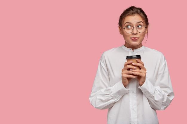 Marzycielski stylowa młoda kobieta w okularach, pozowanie na różowej ścianie