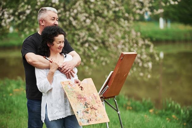 Marzycielski wygląd. starsza para spędza wolny czas i razem pracuje nad farbą w parku