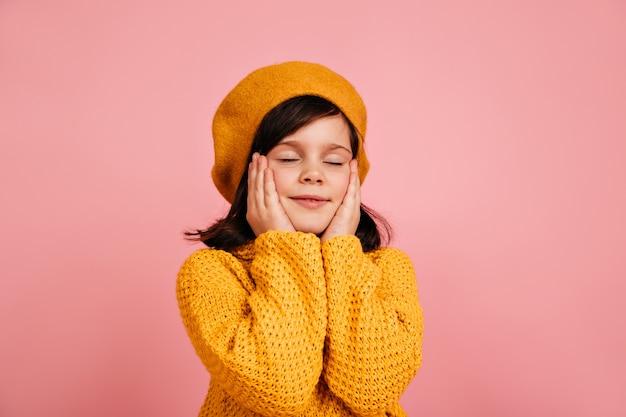 Marzycielskie dziecko pozuje z zamkniętymi oczami. beztroskie dziecko na białym tle na różowej ścianie.