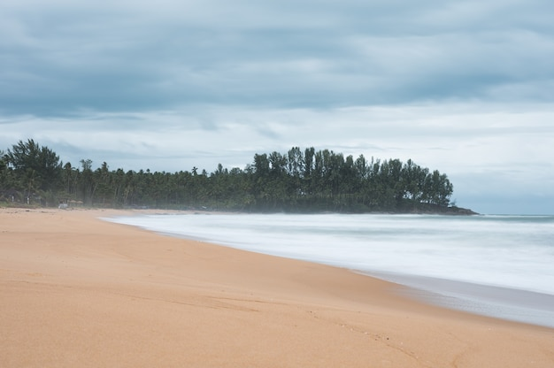 Marzycielskie tropikalne morze z falą pianą na wybrzeżu w ponurą pogodę
