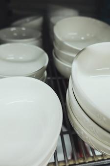 Masa białych ceramicznych misek na stojaku.