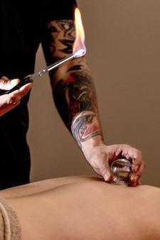 Masaż bańkami. młody człowiek korzystający z masażu pleców i ramion w spa. profesjonalny masażysta leczy pacjenta płci męskiej. koncepcja zabiegów relaksacyjnych, kosmetycznych, ciała i twarzy. masaż w domu.