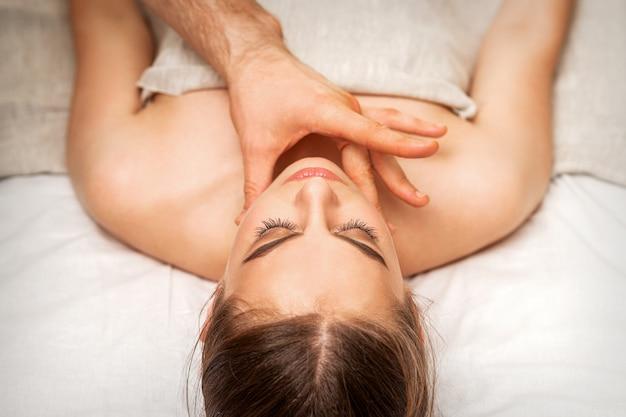 Masaż brody lub szyi młodej kobiety ręką masażysty w salonie spa