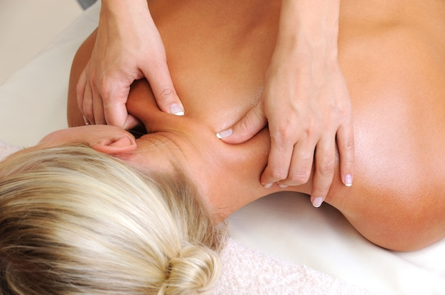 Masaż ciała dla młodej kobiety w gabinecie kosmetycznym