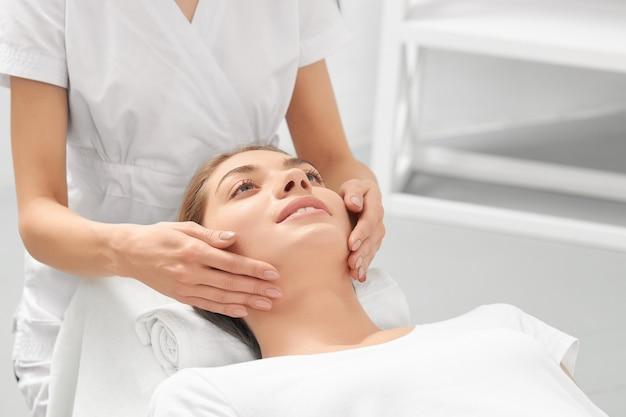 Masaż dłoni dla młodej uśmiechniętej kobiety w gabinecie kosmetycznym