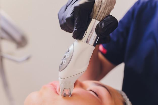 Masaż drenaż limfatyczny proces aparatem lpg. kosmetyczka-terapeutka wykonuje odmładzający masaż twarzy modelki.