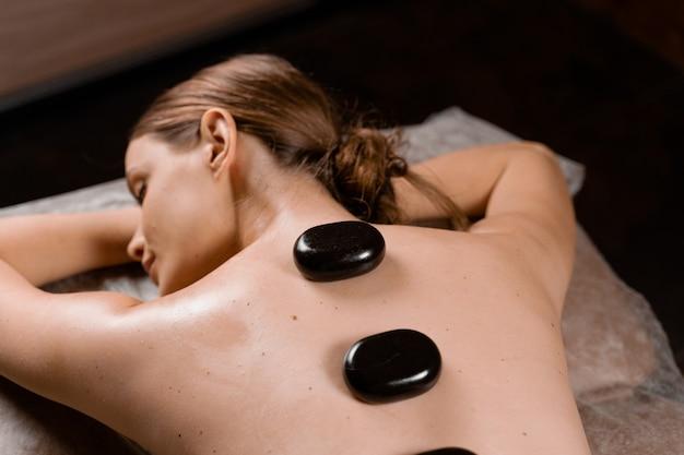 Masaż gorącymi kamieniami relaksuje i rozluźnia napięte mięśnie oraz uszkodzone tkanki miękkie ciała. rozgrzane kamienie umieszczone są na określonych partiach młodej kobiety.