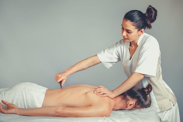 Masaż gua, terapia sha. młoda profesjonalna masażystka wykonuje masaż tajski. pacjent leży na łóżku i jest przykryty białym ręcznikiem. leczenie, odpoczynek, relaks, opieka zdrowotna, medycyna
