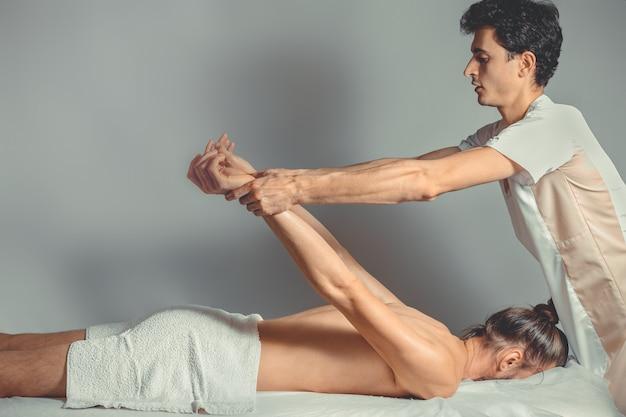 Masaż i terapia rozciągająca młody profesjonalny masażysta sprawia, że pacjent masażu tajskiego kłamie