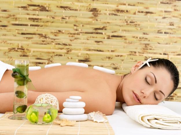 Masaż kamieniami dla młodej kobiety w salonie kosmetycznym spa. terapia rekreacyjna.
