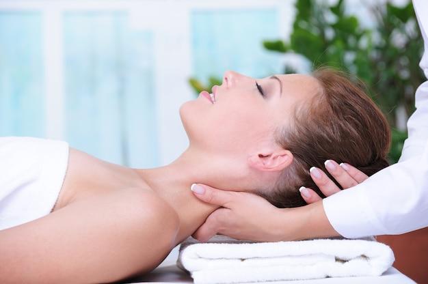 Masaż karku dla młodej kobiety relaksujący w salonie spa