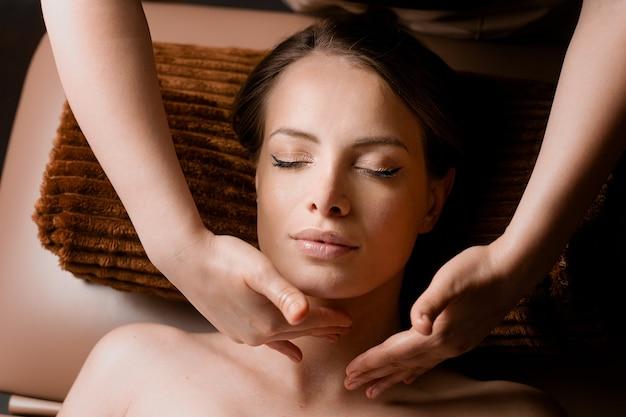 Masaż karku i twarzy w spa. masażysta wykonuje zabiegi upiększające twarz dla atrakcyjnej modelki. relaks.