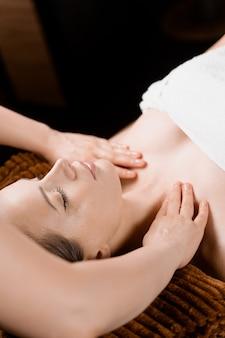Masaż karku i twarzy w spa. zabiegi pielęgnacyjne dla atrakcyjnej modelki. relaks,