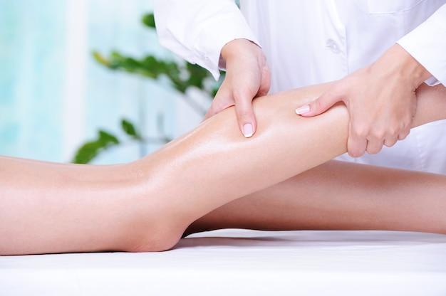 Masaż leczniczy kobiecej pięknej nogi wykonywany przez kosmetyczkę w salonie spa