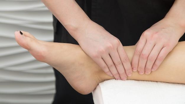 Masaż leczniczy na choroby nóg, zbliżenie. masażystka