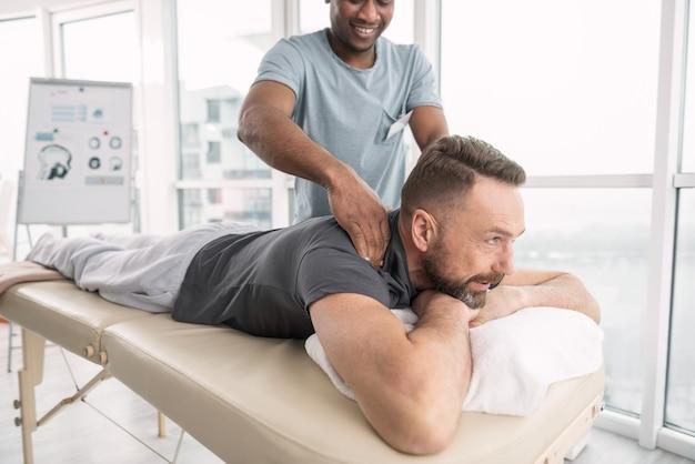 Masaż leczniczy. radosny miły brodacz uśmiechnięty podczas masażu leczniczego