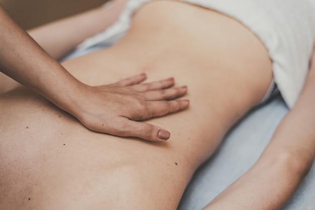 Masaż medyczny kręgosłupa. masażysta masuje nastolatka w klinice
