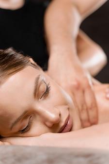 Masaż na 4 ręce w spa. dwie masażystki wykonują masaż relaksacyjny na cztery ręce z olejkiem dla dziewczynki. relaks. terapia manualna.