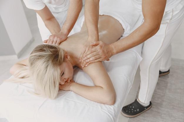 Masaż na cztery ręce. pojęcie opieki zdrowotnej i kobiecego piękna. dwie masażystki wykonują podwójny masaż dziewczyny. kobieta w salonie spa.