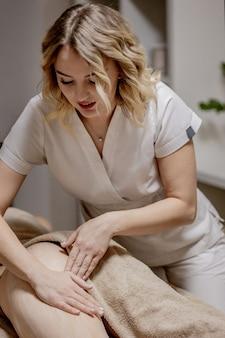 Masaż na problematycznych obszarach ciała w celu utraty wagi i korekty ciała. mistrzyni masażu wykonuje masaż antycellulitowy młodej dziewczynie. zabiegi spa masaże relaksacyjne.