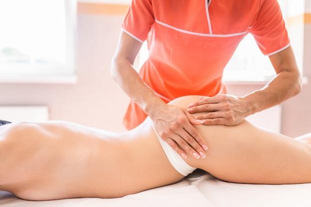 Masaż nóg i pośladków w celu redukcji cellulitu i zachowania zdrowego wyglądu. dłonie kobiety nakładające olej na skórę klientów.