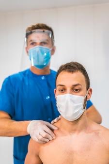 Masaż obojczyka pacjentowi. fizjoterapia ze środkami ochronnymi przeciwko pandemii koronawirusa, covid-19. osteopatia, terapeutyczny chiromasaż