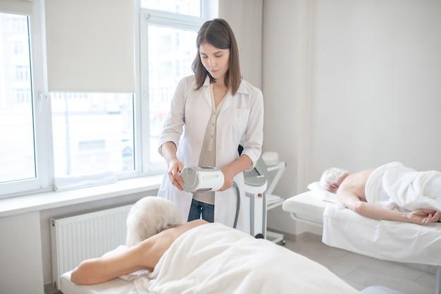 Masaż pleców. młody fizjoterapeuta wykonujący masaż rahabilitacyjny pleców starszych pacjentów
