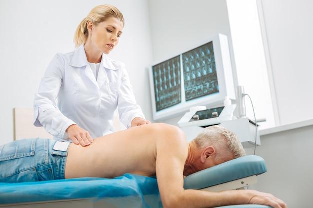 Masaż profesjonalny. miła, przyjemna młoda kobieta, patrząc na kręgosłup pacjenta i uśmiechając się podczas masażu