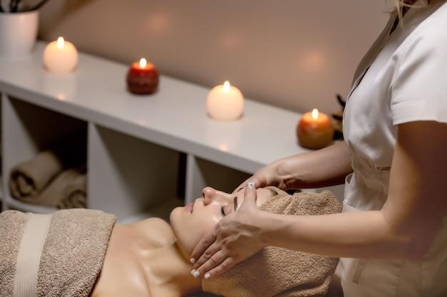 Masaż relaksacyjny. kobieta odbiera masaż głowy w salonie spa, widok z boku.