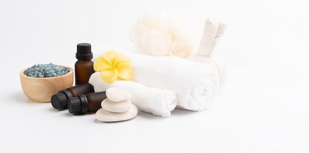 Masaż spa, egzotyczne tropikalne kwiaty plumerii, serum, peeling ziołowy, kamienie zen, białe ręczniki i niebieski kryształ soli na białym tle