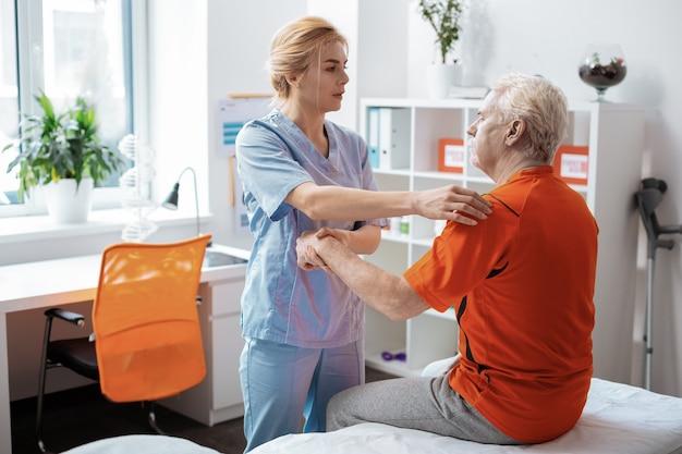 Masaż specjalny. miła młoda kobieta trzymająca pacjenta za rękę podczas wykonywania dla niego specjalnego masażu