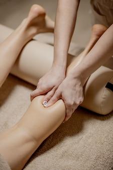 Masaż stóp w gabinecie masażu - kobiece dłonie masują kobiece stopy - uroda i zdrowie.